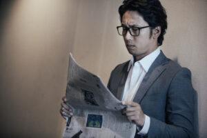 新聞を読むスーツの眼鏡男性