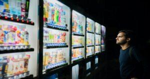 夜に自販機を見る男性