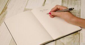 プランを紙に書いて立てる女性
